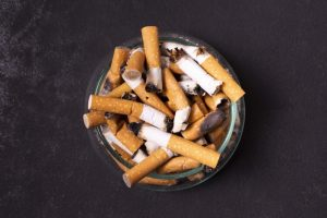 cigarette butts in an ashtray on a dark grey ground