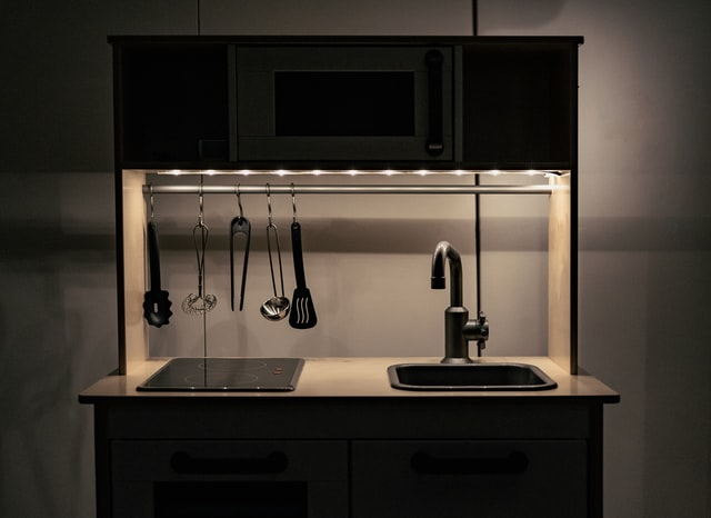 A stainless steel kitchen faucet and an induction stove