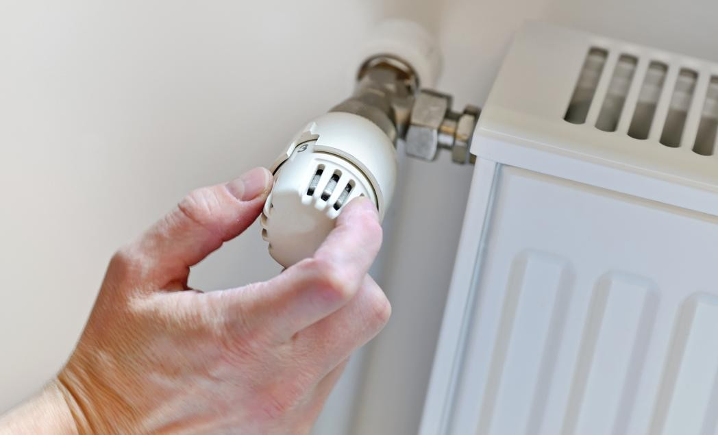A plumber adjusting the thermostat of a water heater.