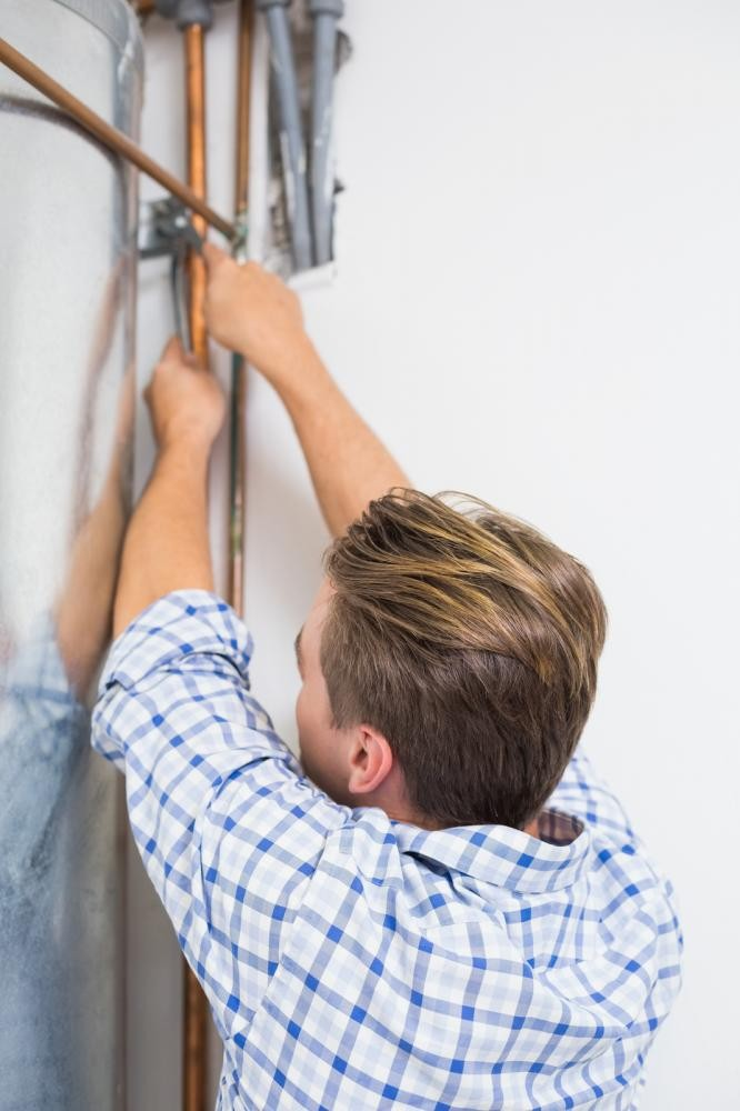 A young plumber repairing a water heater
