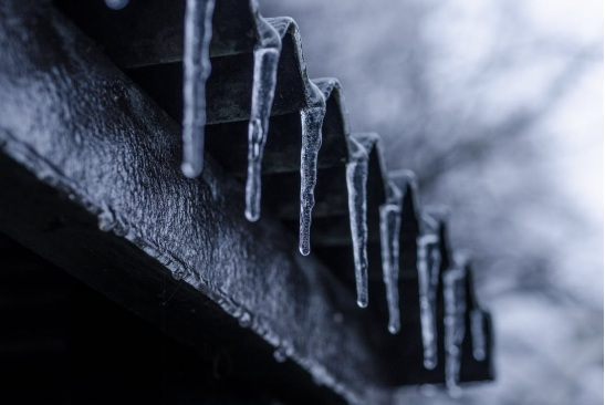 Frozen icicles hanging on a roof's edge