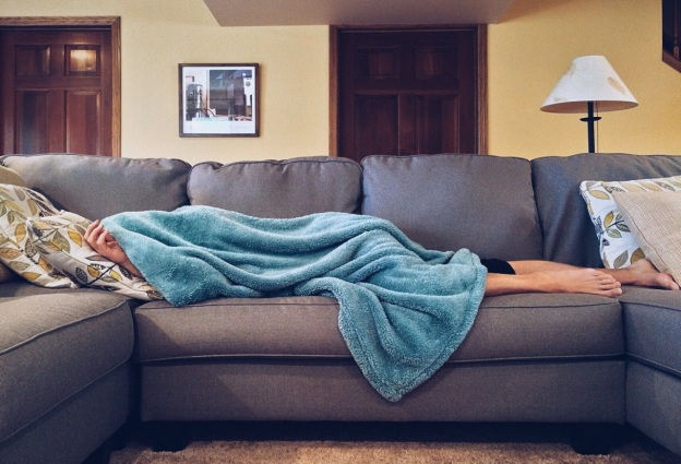 A person lying on the sofa while covered with a blanket