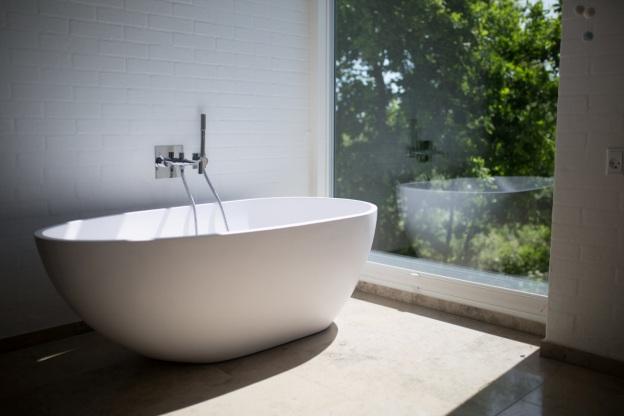 A white ceramic bathtub near a window