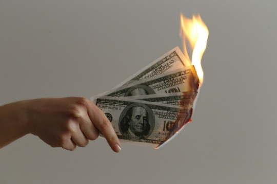 Dollar bills being burned as a sign of losing money