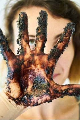 Woman's hand covered in different colored debris