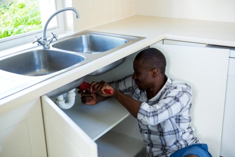 a person repairing garbage disposal under the kitchen sink