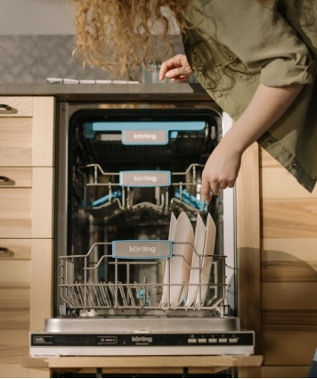 A person putting dishes inside a dishwasher