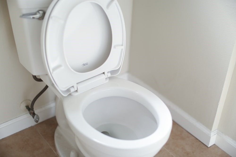 A white toilet with the seat up