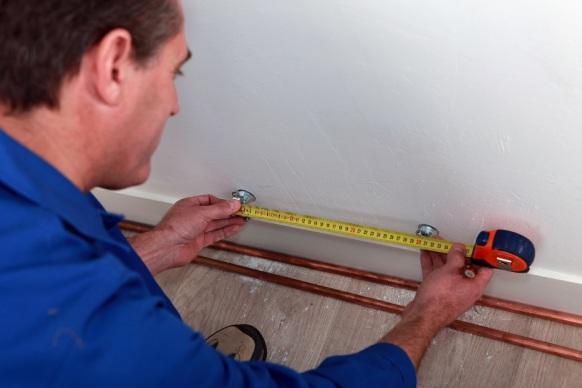 Plumber measuring pipes for repair